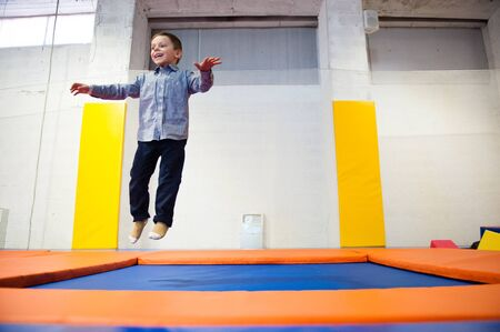 happy laughing little boy jumping on trampoline indoor gym during leisure playful time
