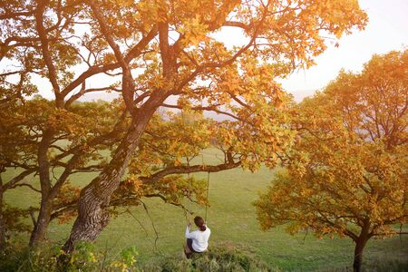 dreamlike fairy concept of young girl swinging on swing on tree with autumn yellow leaves on sunset outdoor leisure activity wellbeing lifestyle