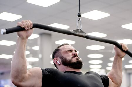 young strong caucasian bearded man with wireless headphones in ears pulling heavy weight on exercise equipment indoor sport gym training