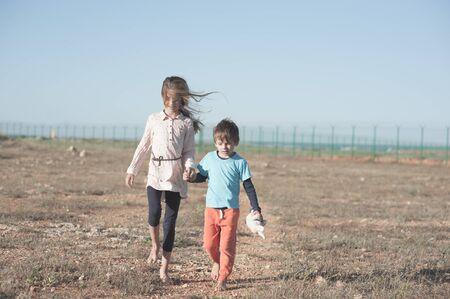 Refugee orphan family boy and girl holding hands walking in hot desert near state border Stock Photo