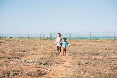 Two poor refugee children boy and girl walking across hot desert with state border fence
