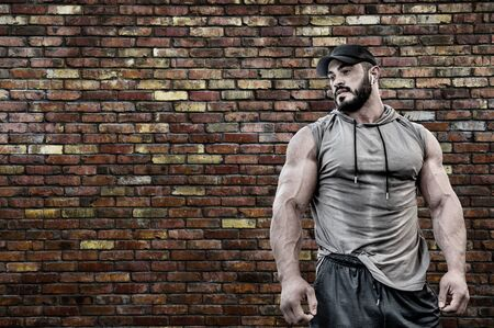 Powerful strong young bearded muscle man in sport hoodie shirt wearing cap and wireless headset with brick masonry old wall with copy space