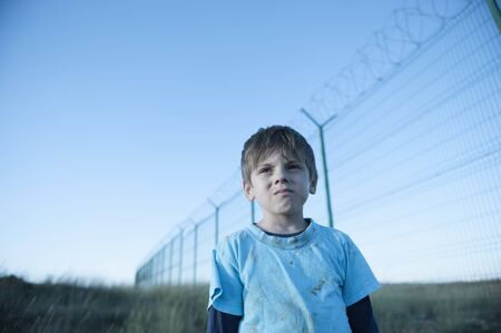 Portrait of poor orphan refugee prisoner migrant child in dirty clothes with sad face near state border with high fence with barbed razor wire Archivio Fotografico