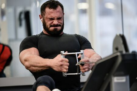 Hard stress motivation sport workout training of bearded strong man with big muscles pulling weight on exercise equipment Imagens