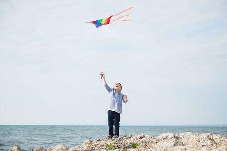 actieve gelukkige kleine jongen met vliegende kleurrijke vlieger die in de lucht vliegt op de kust van de rots op zonnige zomerdag