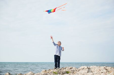 active happy little boy holding flying colorful kite flying in air standing on rock sea shore on summer sunny day