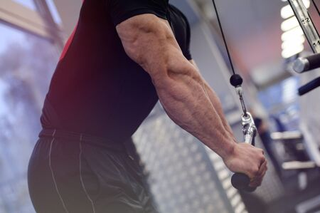 fitness training concept of young strong man pumping iron in sport club gym