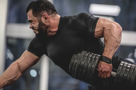 strong young bearded caucasian man in black sportswear pulling heavy weight dumbbell with one hand training back and arms in sport gym workout