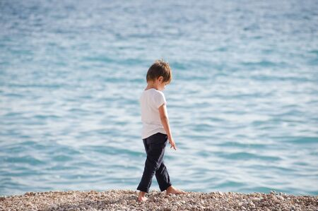 one lonely preschool kid in white jersey and blue trousers walking upset along sea beach in spring Stock Photo