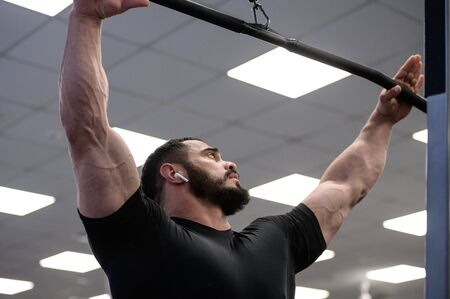 mighty strong male with black beard holding crossbar of exercise machine
