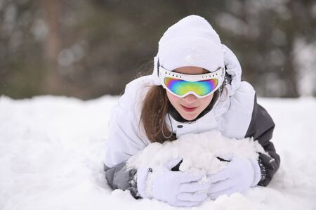 happy smiling beautiful little girl in woolen hat and ski goggles lying in white snow during mountain forest leisure holiday in winter Stock Photo