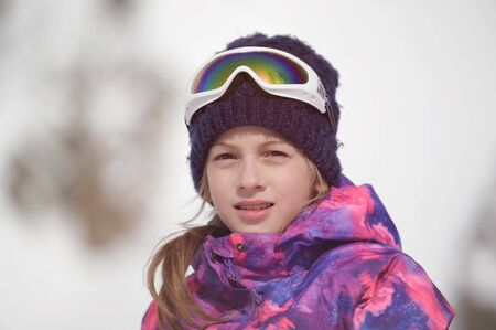 beautiful active smiling happy small young caucasian girl in woolen hat and snowboarding jacket with ski googles during winter outdoor leisure recreation sport vacation Banque d'images - 140588349