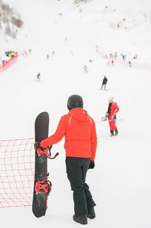 man in black helmet wearing winter sportswear holding snowboard looking at snow mountain with skiers and snowboarder young girl in red clothes
