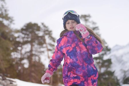 happy active sport healthy little caucasian girl in wool hat ski goggles and snowboarding jacket running in winter forest with trees