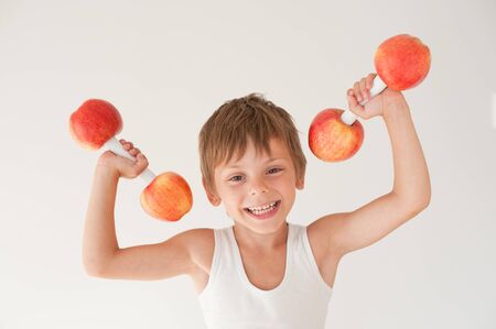happy smiling active strong little child in tank top lifting dumbbell made of apple during sport training workout