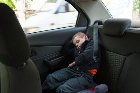 little boy in sweater sleeping in car with window with seat belt