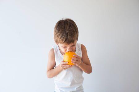 active sport healthy kid in white tank top biting eating orange fruit