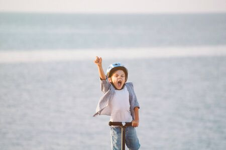 happy succeed little boy in sport helmet standing on sea background with scooter with hand up for success victory winner concept