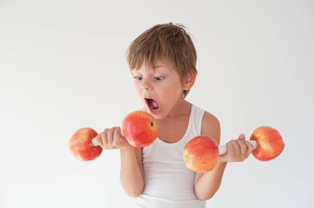 hungry active strong small child in tank top lifting dumbbells made from apple fruits wishing to bite