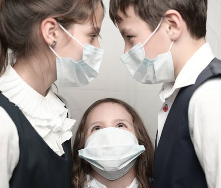 COVID-19 coronavirus concept of three little kids in medical masks and school uniform