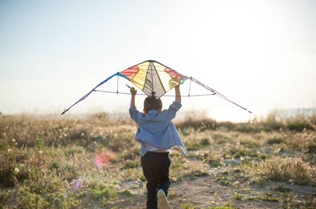 active little boy with color kite running towards bright sunset and sea shore trying to fly
