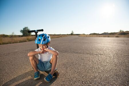 sad little active kid in sport protective helmet sitting lonely on scooter on empty desert summer asphalt road on hot sunset