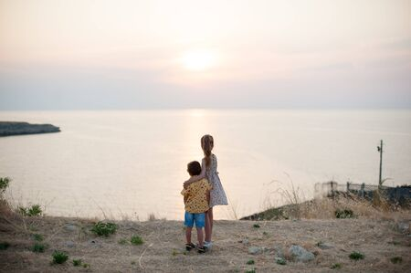 care and love concept of two little children boy and girl hugging on sea shore looking at warm summer sunset