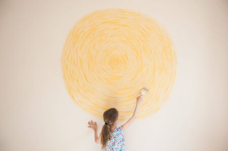 creative art hobby and leisure concept of little girl painting yellow sun on home wall indoors during covid-19 quarantine with copy space