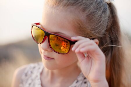 beautiful small girl look at her little kid brother through summer sunglasses 版權商用圖片