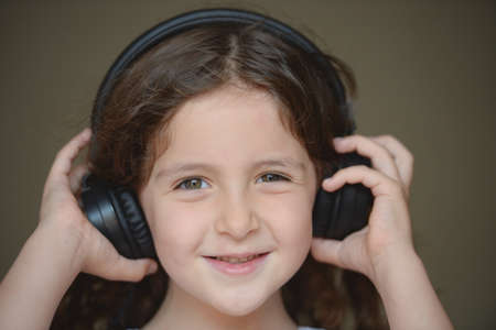 stay at home during lockdown quarantine happy smiling small girl listening music in black headphones Foto de archivo