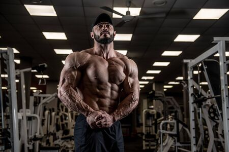 muscular male physique concept of strong athlete showing big muscles in empty gym Foto de archivo