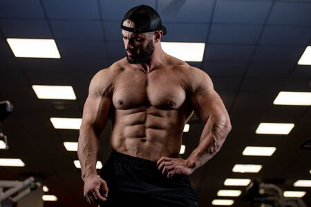 strong young bearded man with perfect abdominal muscles in blue lit sport gym