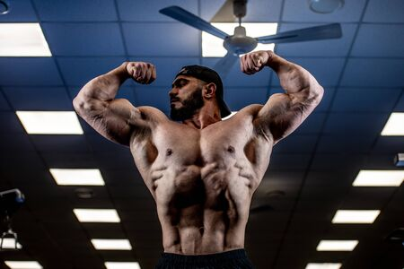 muscular strong male with beard show his big biceps muscles in blue lit sport fitness gym