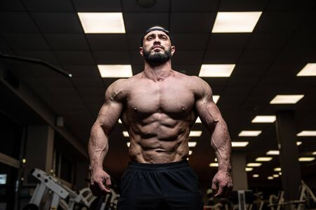 young bearded athlete with strong muscles in dark fitness club gym