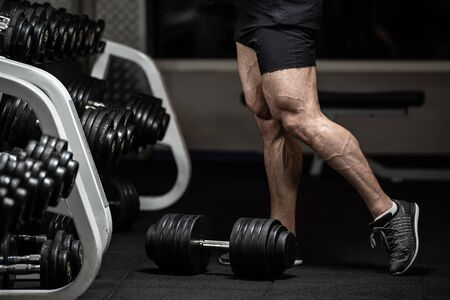 healthy body part concept of young strong bodybuilder legs in trunks and sneakers near dumbbells in fitness gym