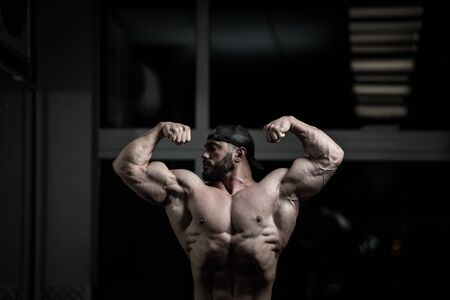 handsome active strong bearded man in cap showing double biceps muscles in dark fitness gym