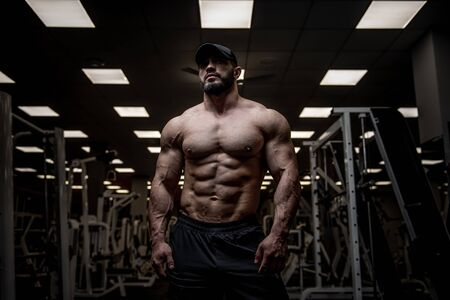 handsome young strong bearded male in dark sport empty gym with fitness equipment indoors