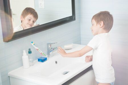cute healthy caucasian little kid in white tank top standing leaninng washbasin in bright blue bathroom with mirror and beautiful flare Archivio Fotografico
