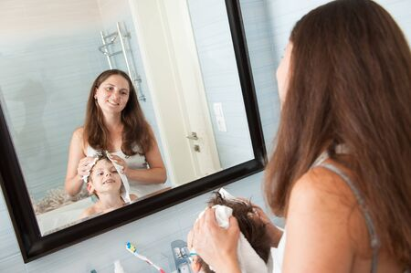 beautiful family caucasian mother woman dry off her little boy hair in bathroom look at mirror with smile