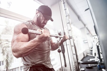 sport motivation concept of powerful focus bearded man training his biceps muscles in sport gym Stock Photo