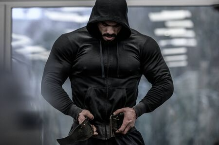 strong young bearded mighty man in hoodie wearing powerlifting belt for heavy hardcore weight training workout indoors sport fitness gym