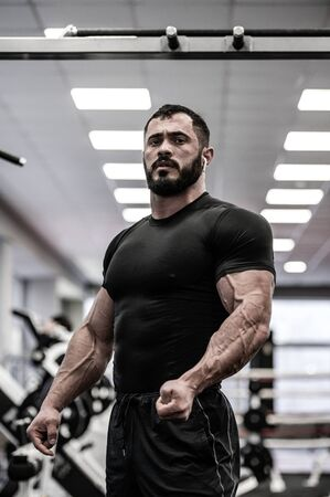 young bearded athlete in black jersey with strong muscle an vein in gym during posing Banco de Imagens