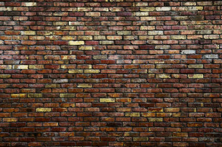 masonry concept of vintage aged brick wall of red and yellow color in urban darkness with copy space Foto de archivo