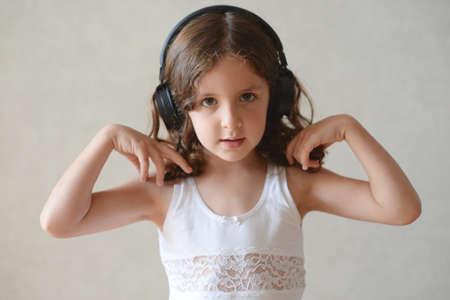 beautiful little caucasian girl singing and dancing listening music using black headphones during home self isolation quarantine Foto de archivo