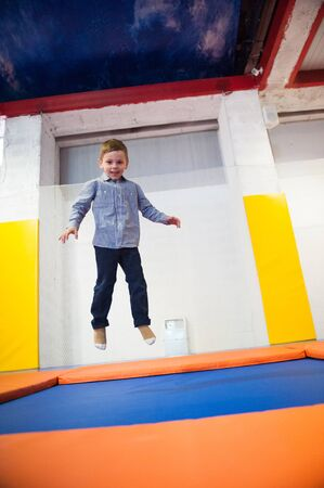 happy cute healthy little boy jumping on a trampoline indoors