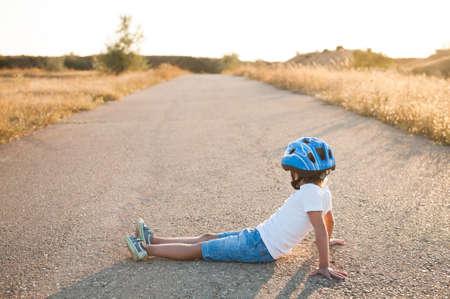 tired little kid wearing sport equipment helmet and sneakers sitting on empty asphalt road on summer warm sunset