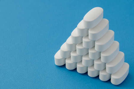 pyramid from many white vitamin drugs medication tablets on blue pure surface with copy space