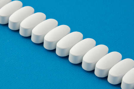 pharmacy concept of row of white vitamin tablets drugs lying on vivid blue color surface