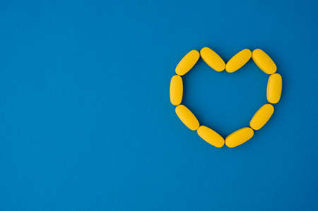 cardio health care concept of yellow pills tablets in heart form on blue surface with copy space