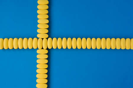 concept healthcare of yellow tablets on blue surface with copy space in form of cross on sweden flag Foto de archivo